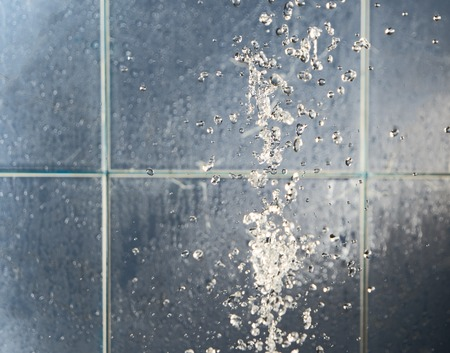 levitate: Water drops splash levitate on blue bathroom background