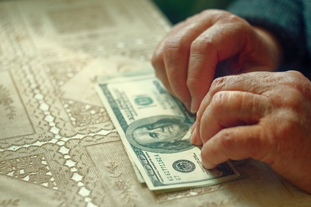 latina america: Senior retired woman with small amount of money on table, toned image, colorized, selective focus, very shallow dof