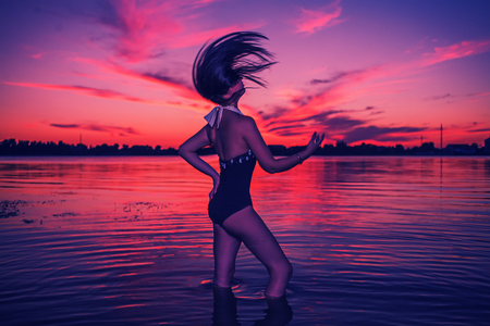 Teenage Girl Playing with Water in Sea at Sunset Shaking her Head. photo