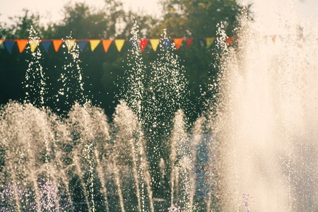 city park fountain: Vintage holidays shot. Jets of a city park fountain and colorful flags