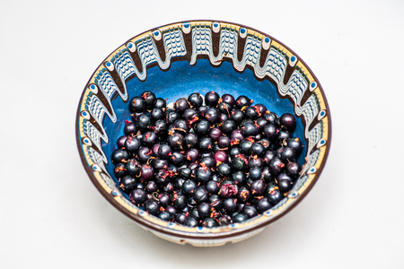 bilberries: Bilberries in small ornate bowl on white background