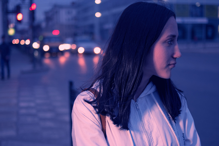 colorized: Young woman looking away against a night city lights. Defocused carlights on background. Vintage color. Toned image. Colorized. Stock Photo
