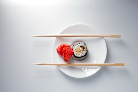 small plate: Sushi roll on small plate with chopsticks on the side and a lot of space for text