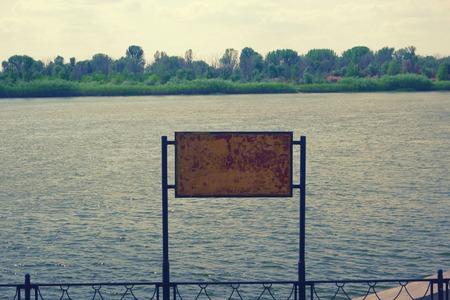 Rusty billboard against summer river. Vintage color. Colorized, toned image. Zdjęcie Seryjne