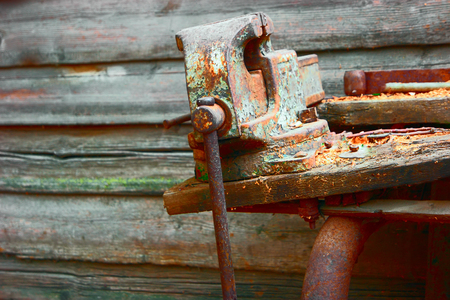holdfast: Old rusty vise on workbench of obsolete wood, a lot of space for text, copyspace