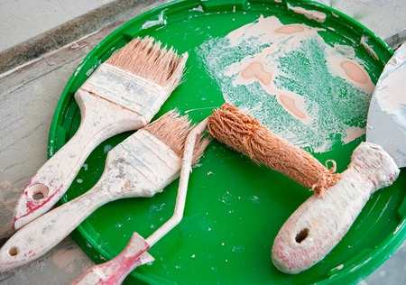 platen: Used brushes, roller for paint on green plastic cover Stock Photo