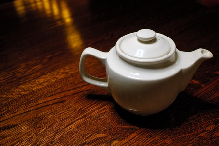 fireclay: Teapot on old wooden table against the background of dark room.