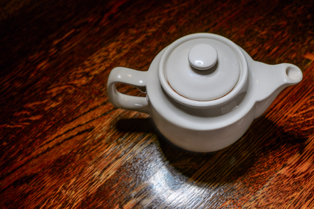 fireclay: White teapot top view on vintage wooden table with copyspace.