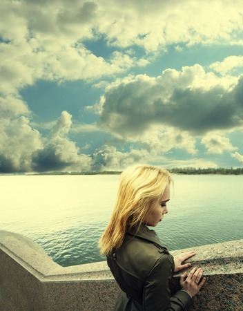 ander: Pensive woman leaning on granite sea-wall ander sky with clouds, toned image, profile view