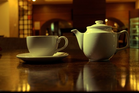 colorized: Tea time. White teacup and teapot on the wooden table in dark room, side view, toned image, colorized shot