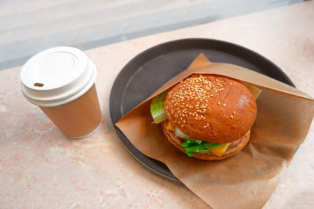 breakfast cup: Hamburger in paper and takeaway coffee cup. Hot drink cup and tasty burger. Small breakfast in cafe.