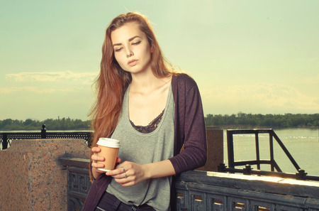 brown haired girl: Portrait of beautiful brown haired girl standing and looking down. She keeping takeaway drink. Urban city scene. Outdoors portrait vintage film color imitation. toned image, colorized