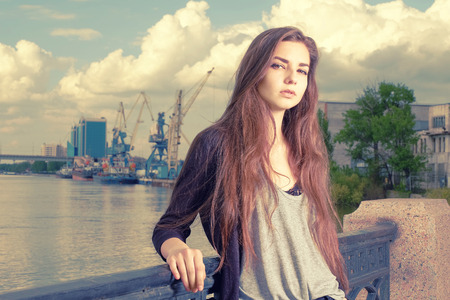 frowned: Lonely girl waiting for your. Wearing light gray shirt, black jacket, an young american woman standing by metal fence on pier in New York, frowned, with port cranes on background. Stock Photo