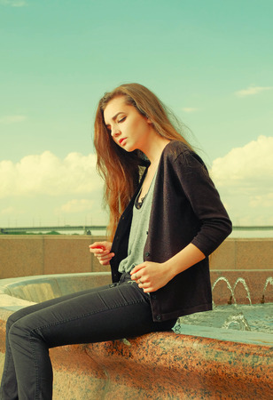 waiting posture: Lonely girl wants someone to talk. Wearing light gray sweater, black pants, an youg american woman sitting on red granite fountain, sad, depressed, listening to sad thoughts.