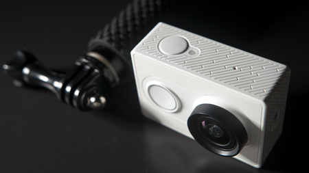 cam gear: Action camera unrecognasible brand and small monopod head on black background, selective focus Stock Photo