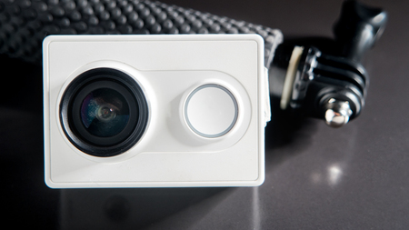 cam gear: Action camera and small monopod head on black background, selective focus, front view. Unrecognasible brand camera.