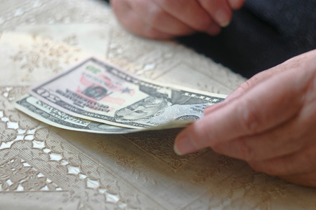 latina america: Retired woman with small amount of money on table, toned image, colorized, selective focus, very shallow dof. SEnior woman counting dollars. Stock Photo