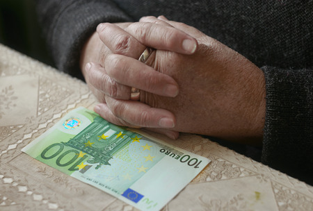 colorized: Elderly hands and hundred euro bill on the table, selective focus, shallow depth of field, toned colorized shot.