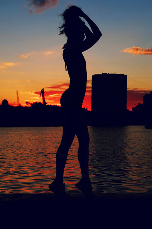 embankment: Portrait of young woman as silhouette by the river. Slim sporty girl is posing in river embankment in front of colorful sunset.