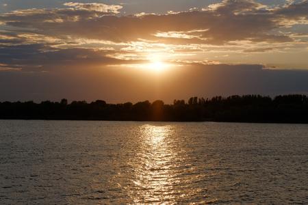 Sunset ove Volga river in Russia. Orange clouds in sunset time. Nightfall. Stock Photo