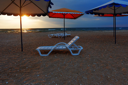 deserted: Beach loungers and umbrellas on deserted coast sea at sunset. Stock Photo