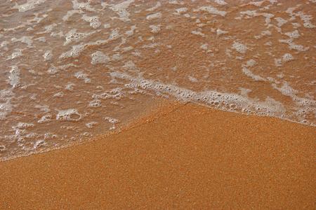 Vague de mer sur une plage de sable avec mousse, beaucoup d'espace pour le texte