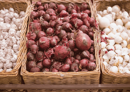 cebolla blanca: Bunch of red onion, white onion and garlic in wicker tray in supermarket.