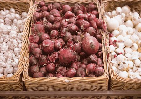 cebolla blanca: El manojo de cebolla roja, cebolla y ajo blanco en la bandeja de mimbre en el supermercado.