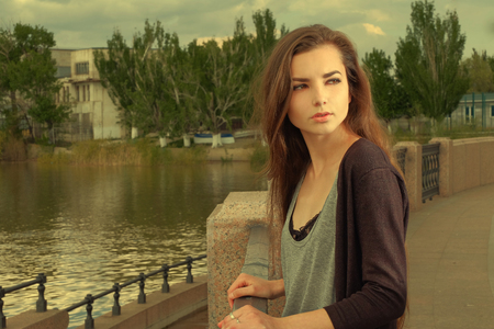 Pretty girl wearing black shirt, standing against fence by Volga River in Astrakhan in summer, looking back