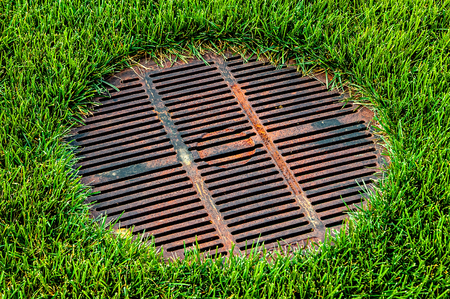 Gridded sewer manhole on green lawn.