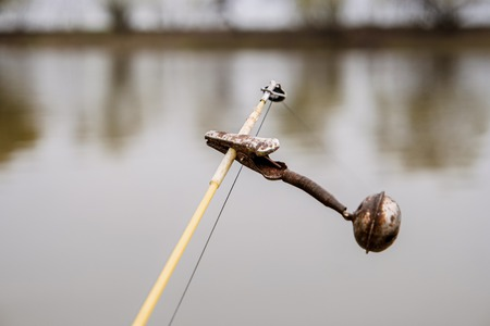 The bell on the top of fishing rod in front of water surface. Old spinning equipment. Selective focus, shallow DOF.
