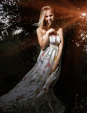 Happy girl in white dress in front of dark trees, magical look photo