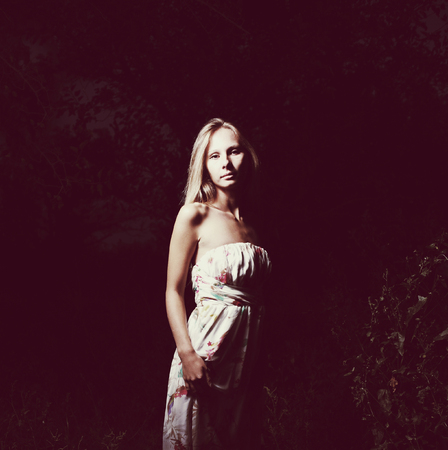 Depressed woman in white dress in the dark, adness concept, colorized shot photo