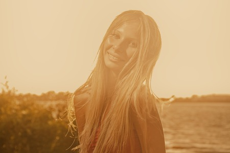 Low contrast shot of happy long haired woman on the summer beach looking at camera, image full of sunset sunshine. photo