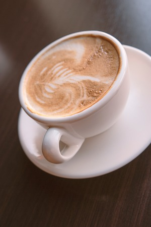 Cup of cappuccio coffee foam art over the black tabletop background with small copyspace Stock Photo