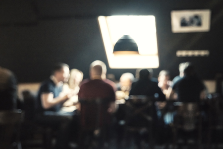 round chairs: Customers at restaurant sitting around a table in front of bright window blur background with bokeh effect. Blurred cafe background