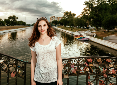Young ginger haired woman on bridge with love locks on fence looking at camera.