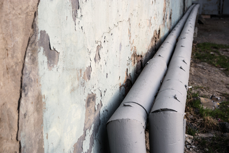 Water Pipes With Renewed Thermal Insulation And Room For Text On Grungy Wall