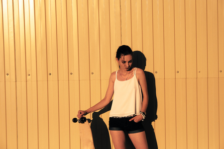 Girl in denim shorts and tank top standing with skateboard in front of yellow mwtal fence and looking down a lot of space for text