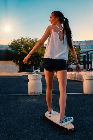 Beautiful girl riding skateboard in short denim shorts, view from back in front of early evening sky Reklamní fotografie