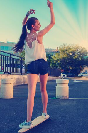 Back view of young girl in short overalls with long bare legs and long hair in ponytail riding skateboard with her hands rised, skater girl trying to keep balance Reklamní fotografie