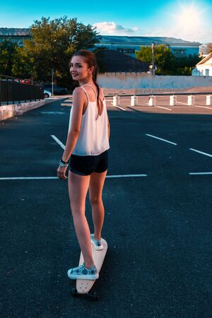 Rear view of young girl in short denim shorts with long bare legs and long hair in ponytail riding skateboard and looking back