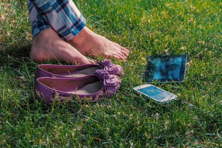 Barefoot girl relaxing on grass cross-legged with tablet-pc and smartphone lying near