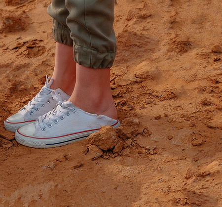 Girls legs in trainers on bare dirt, shot with copyspace