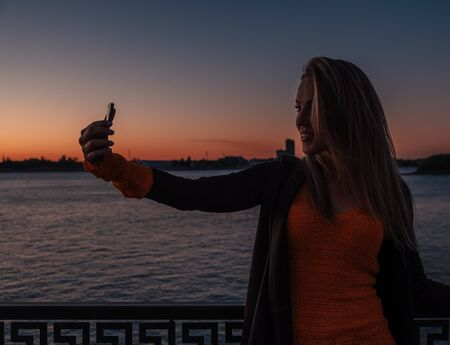 Pretty young female in knitted sweater holding takes selfie while on city street at night in front of river sunset
