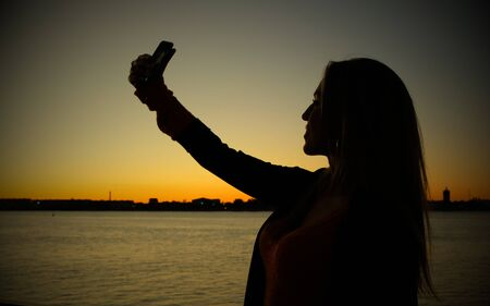 Silhouette of young woman taking selfie in front of sunset river, retro looking image with harsh vignette