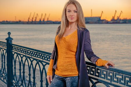 Happy woman wearing knitted jacket of sunset color standing on ocean pier and looking to the camera Foto de archivo - 150553137