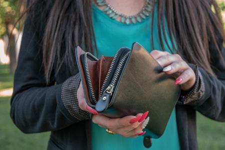 Girl looking into small fashion handbag