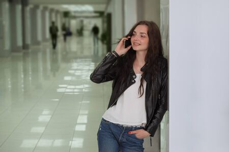 Joyful woman getting great news on phone call. Happy woman in casual wear speaking on cellphone near office corridor and smiling at camera. Good news concept Фото со стока