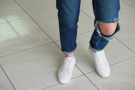 Woman posing in jeans and sneakers while walking with motion blur on one foot